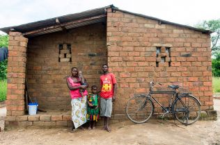 Charles, a former mukula logger, and his family in front of their brick house and bicycle
