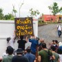 """People hanging a sign that reads """"Chiang Mai Urban Farm"""" in Thai."""
