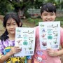 Two girls showing signs with images of plants.