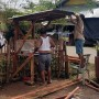Two men work constructing a structure of wood and sheet iron