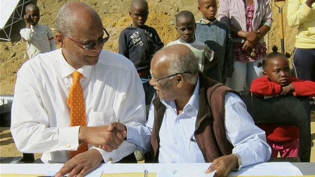 Jockin Arputham, right, signs documents with Stellenbosch Mayor Sidego in South Africa