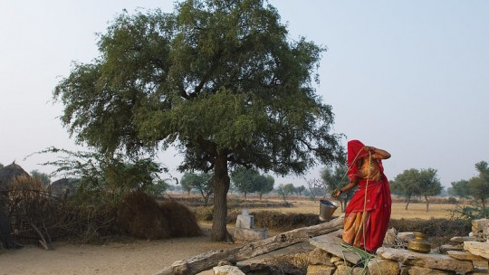 Woman collects water from a well