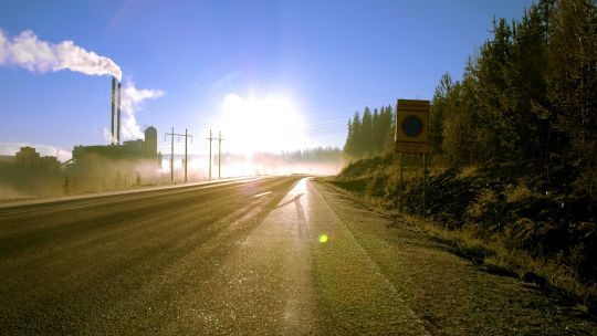A road with a factory and dazzling sunlight in the distance