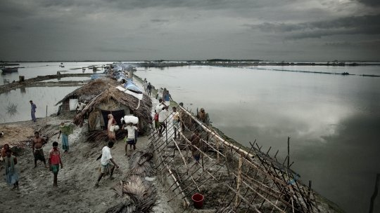 People build temporary shelters on the edge of the Bay of Bengal following a cyclone and flooding.