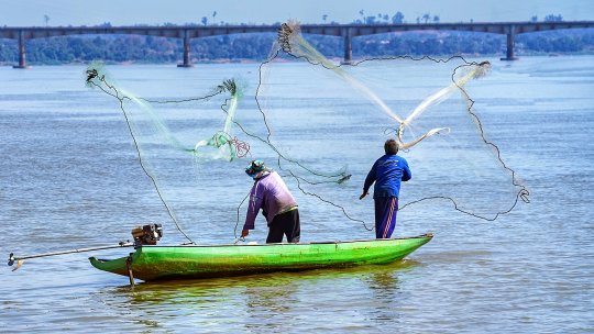 Two fishermen cast their nets from a small boat