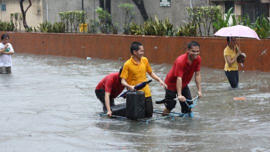 People walking down a flooded road