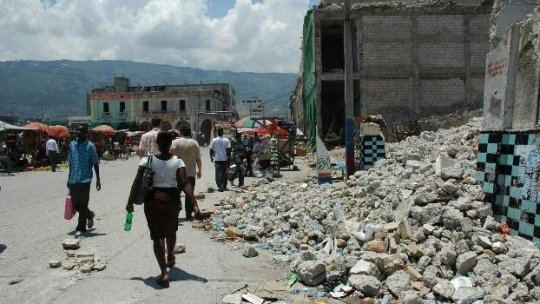 People walk past ruined buildings