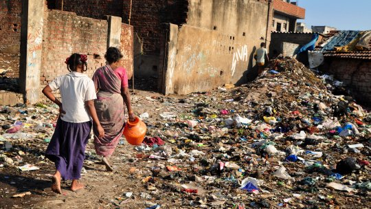Two women walking in a slum