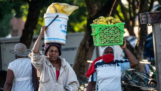 Two people carrying containers on their heads