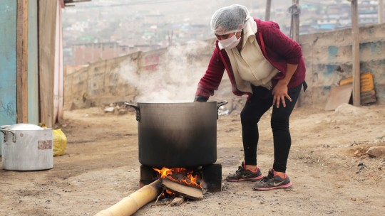 a woman checks an improvised open-air stove.