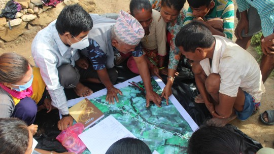 A group of people looking at a satellite map.