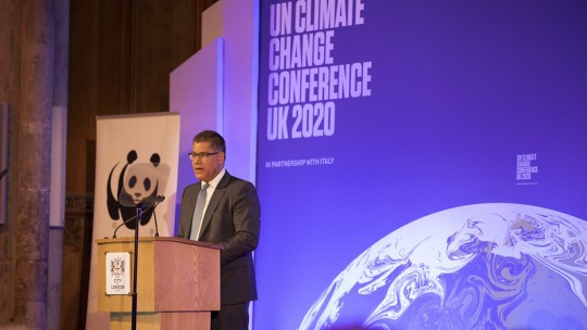 """Man speaking in front of a wall that reads """"UN Climate Change Conference UK 2020"""""""
