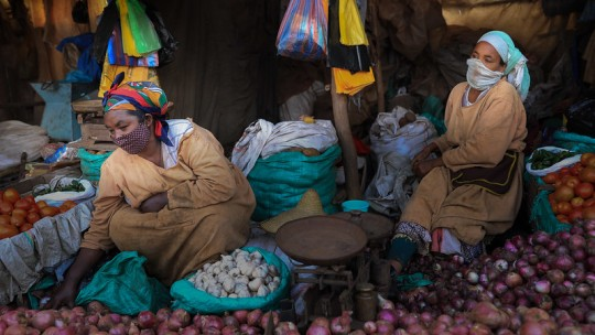 Women sit next to piles of vegetables like onions, tomatoes, garlic.
