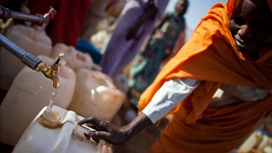 Woman filling a jerry can with water