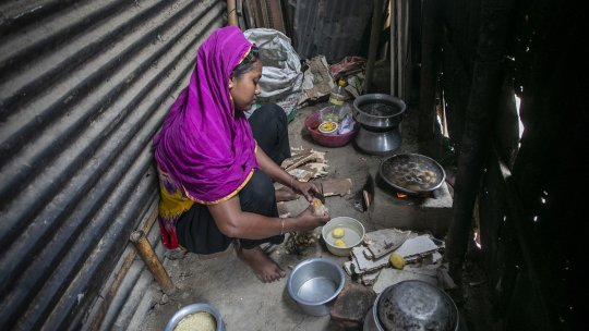 a woman prepares food in an alley