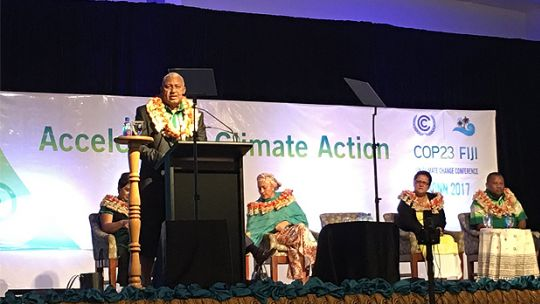 Fiji Prime Minister Frank Bainimarama speaks at the podium at the start of the pre-COP23 ministerial meeting. He called for a coalition of partners to reach 1.5 degrees (Photo: Achala Abeysinghe/IIED)