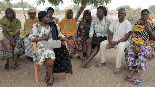 A group of seated African women gather for a discussion