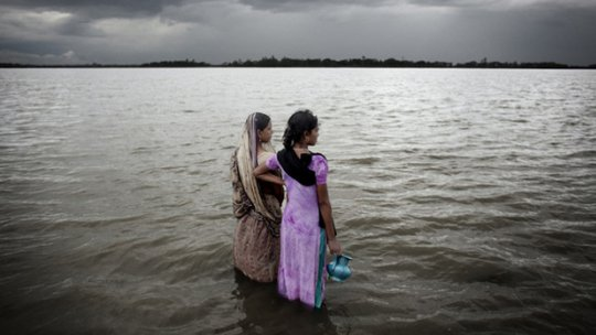 Two women look out over the rising sea water