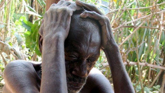 A Batwa man sits with his hands cupping his head