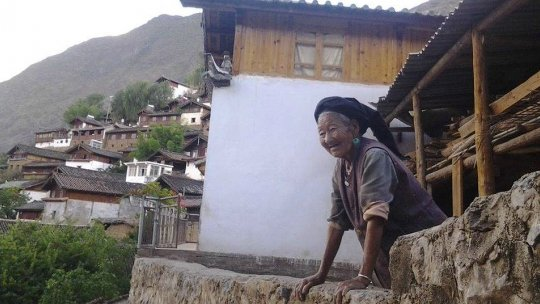 An elderly woman leans out over a stone ledge, with mountains behind her