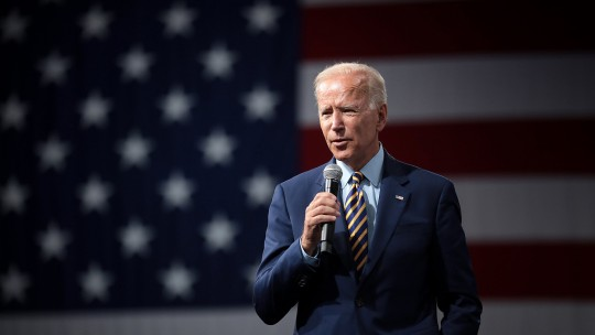 Joe Biden stands speaking into a microphone in front of a large United States flag