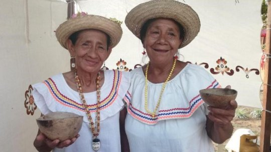 Two women show off food with their arms around one another