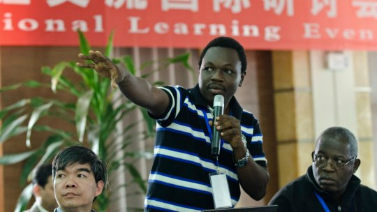 An African man makes a speech in front of a banner in Chinese