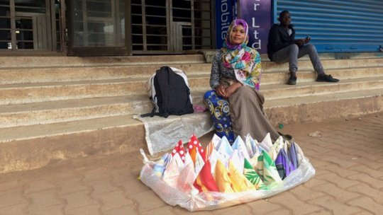 A woman sitting on steps, with colourful handkerchiefs arranged in front of her.