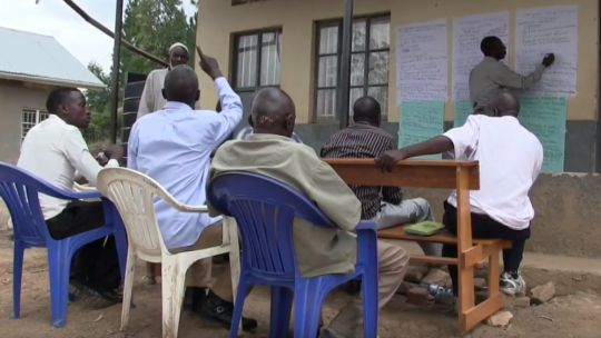 People sitting on outdoor chairs gather around and contribute views as one person writes up their points on paper pinned to the wall