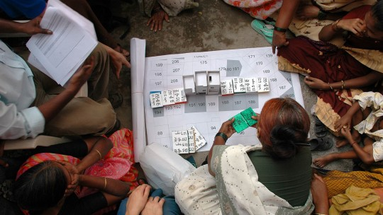 People sit on the floor around a map laid out on the floor