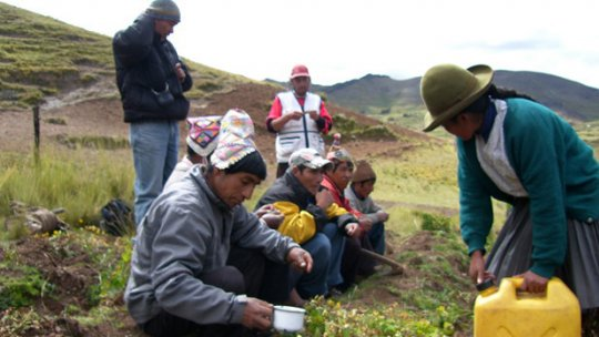 Peruvian men and women on a mountainside, pouring water on the earth