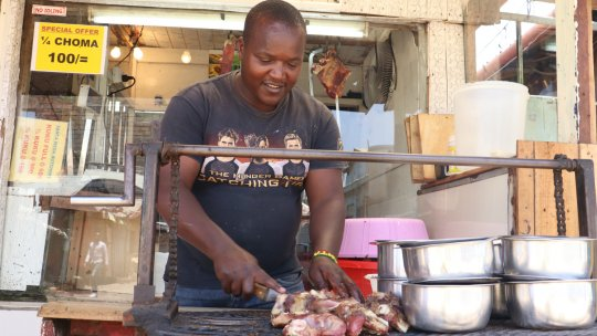 A man behind a counter chops meat