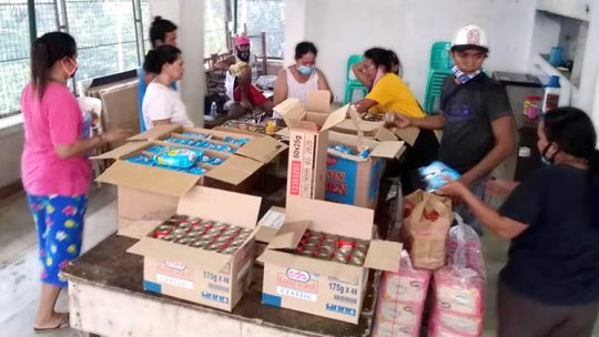A group of people gathered around cartons of food
