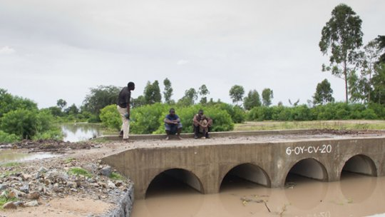 Three men stand on a bridge over an open culvert