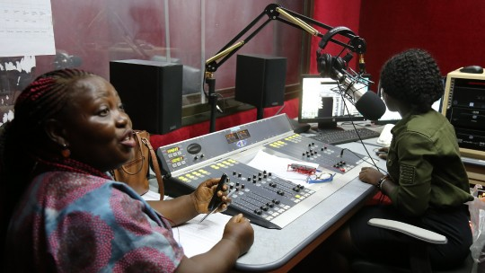 Two woman sit at a radio production desk