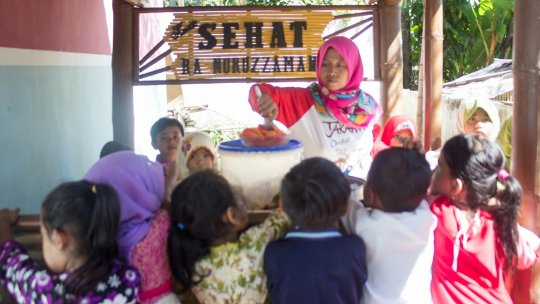 A woman cooks in front of a group of children clamouring for food