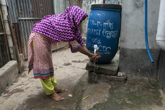 a woman washes her hands at a plastic water butt