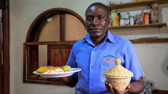 Vincent Semakula holding a plate of food.