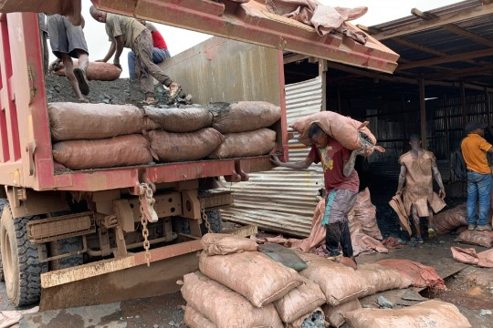 Men load a truck with heavy bags