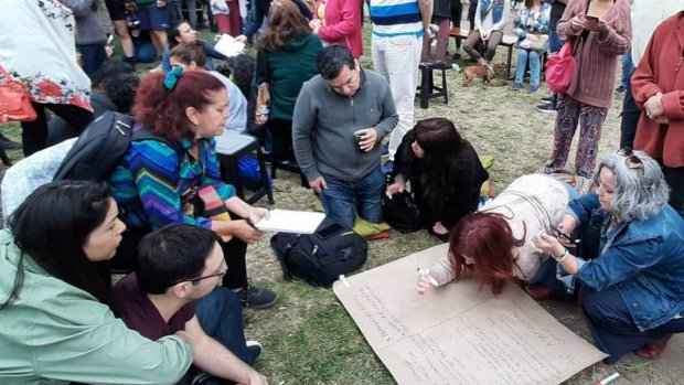 A group of people sit on grass and write on a large piece of paper