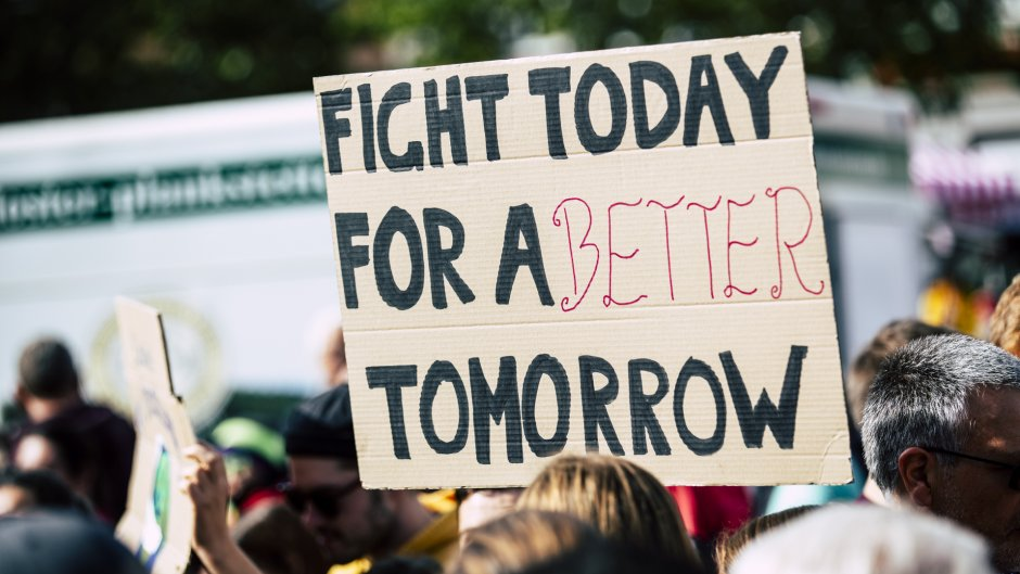 "A handwritten sign is help up saying ""Fight today for a better tomorrow"""