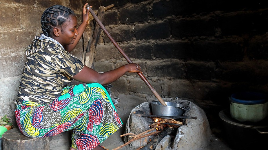 Woman stirs a long stick in a pan on a fireplace made of stone