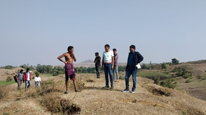 A group of people gather on top of a hill.