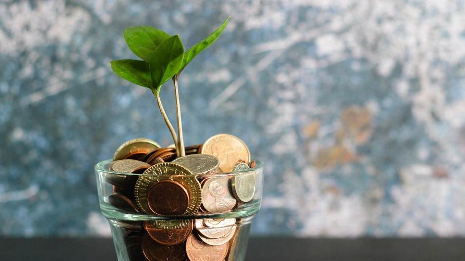 A glass full of coins, with a plant sprouting out of the top